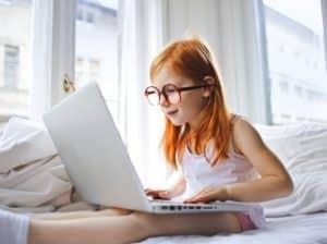 petite fille sur ordinateur dans son lit