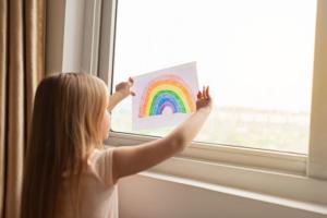 Jeune fille tient un dessin d'arc en ciel dans la fenetre